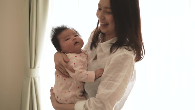 young mother loving her baby girl at home - japanese mom stock videos & royalty-free footage