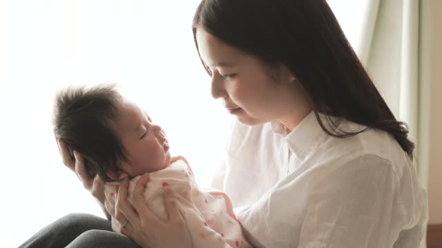 愛する若い母親 彼女のベビーガールご自宅で - 気にかける点の映像素材/bロール