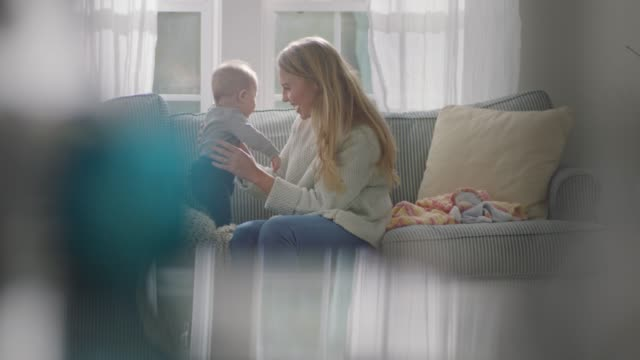 stockvideo's en b-roll-footage met slo mo. young mother lovingly talks to baby on living room sofa. - zorgzaamheid