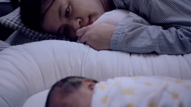 Young mother lying on bed with baby boy (0-1 months)
