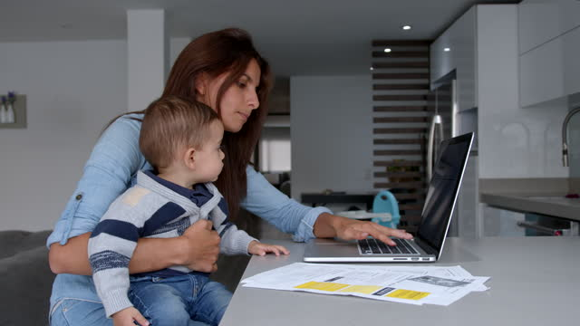 young mother paying bills online while carrying her baby on lap - tired stock videos & royalty-free footage