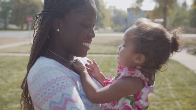 cu young mother playing outdoors with her daughter - braided hair stock videos & royalty-free footage
