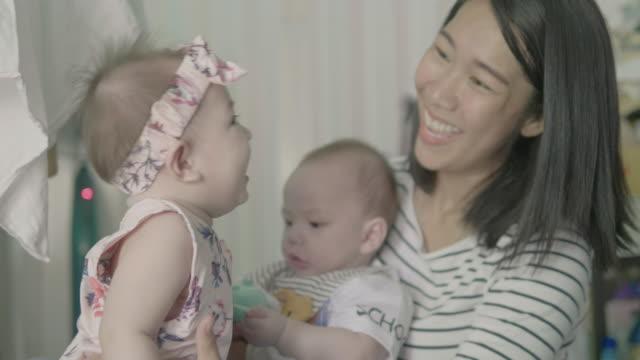 junge mutter spielt mit ihren entzückenden identischen zwillinge jungen und mädchen. - weibliches baby stock-videos und b-roll-filmmaterial