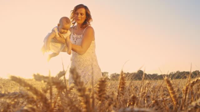 vídeos de stock, filmes e b-roll de jovem mãe brincando com seu bebê no campo de trigo - cereal