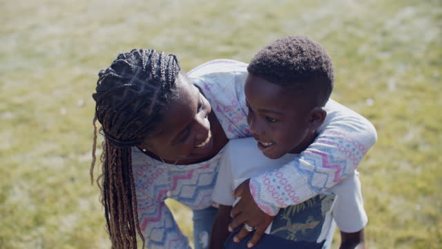 young mother playing with her son outside. - black hair stock videos & royalty-free footage