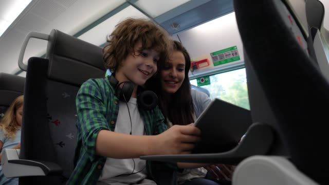 young mother playing with her son using a tablet talking and laughing while commuting on train - russian ethnicity stock videos & royalty-free footage