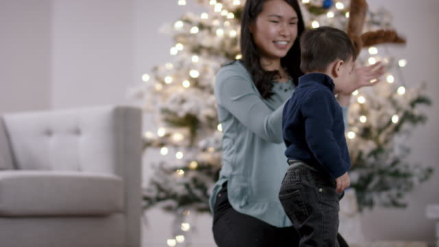 vidéos et rushes de jeune mère jouant avec son enfant en bas âge devant l'arbre de noel - son