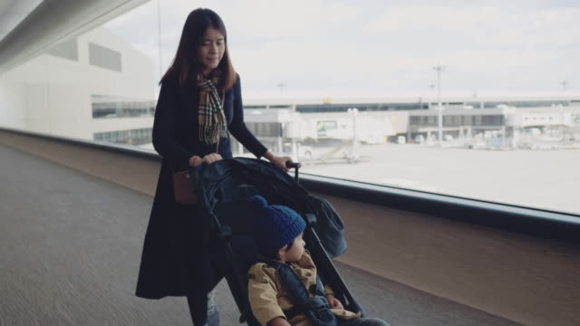 young mother pushing baby stroller with her son in airport stroller - pushchair stock videos & royalty-free footage