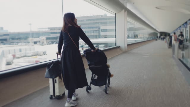 young mother pushing baby stroller with her son in airport stroller - randoseru stock videos & royalty-free footage