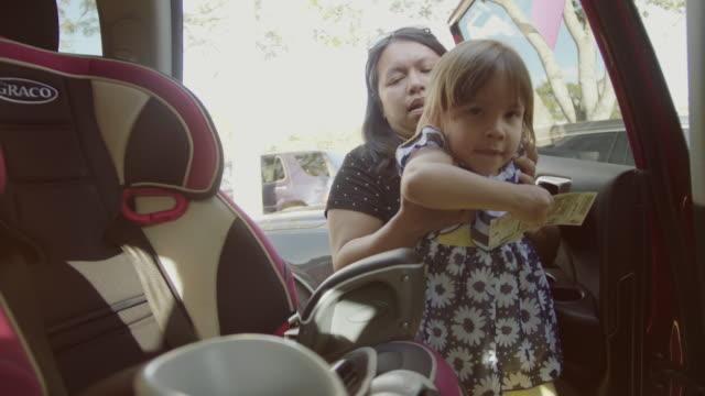 vidéos et rushes de jeune mère fille de mettre dans le siège auto sur la voiture aller à l'école. - reprise des cours