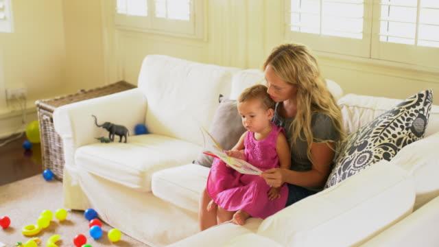 vídeos y material grabado en eventos de stock de ws young mother reading a book to her daughter. - en el regazo