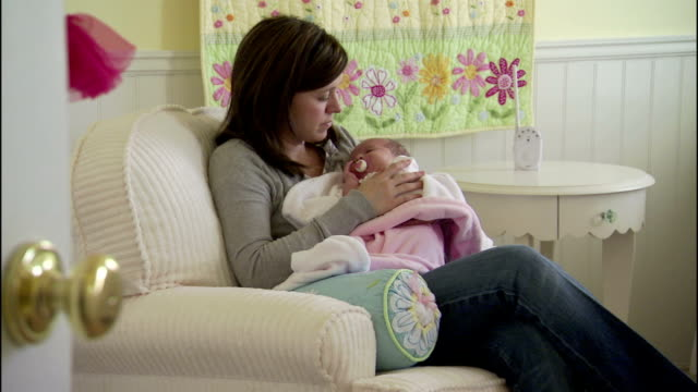 a young mother rocks and cradles her sleeping baby. - nursery bedroom stock videos & royalty-free footage