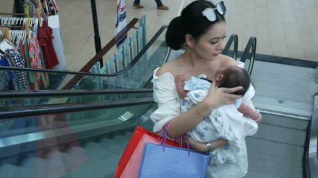 junge Mutter einkaufen und tragenden Neugeborenen auf Rolltreppe