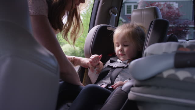 young mother strapping her toddler into a carseat - fatcamera baby stock videos and b-roll footage