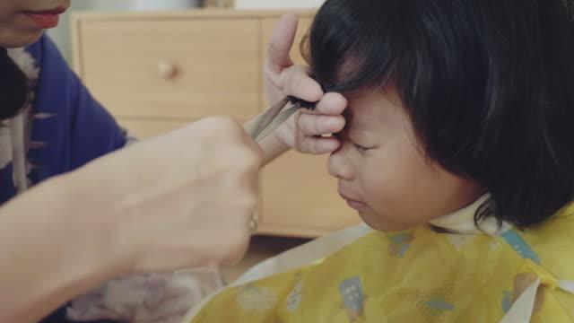 vidéos et rushes de jeune mère coiffant ses cheveux de fils à la maison. - rester à la maison expression
