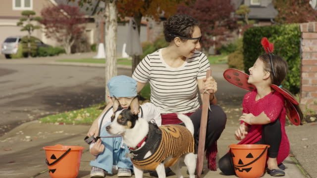 young mother taking her children trick or treating on halloween - stage costume stock videos & royalty-free footage