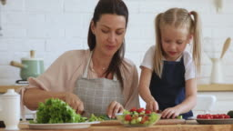 Young mother teaching kid daughter cutting fresh salad in kitchen