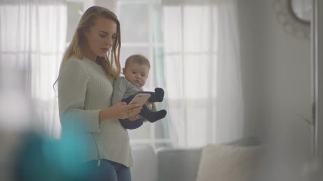 young mother types on smartphone while carrying baby around home living room. - handheld stock videos & royalty-free footage