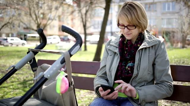 Giovane madre utilizzando il telefono cellulare nel parco