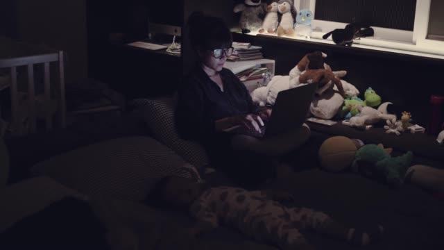 vidéos et rushes de jeune maman à l'aide d'ordinateur portable avec son fils dormir sur le lit la nuit. - faire un somme