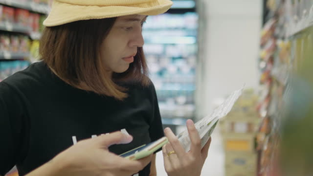 Young mother using smartphone in supermarket with her boy.