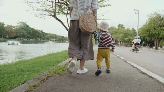 young mother walks with her son on sidewalk - young family stock videos & royalty-free footage
