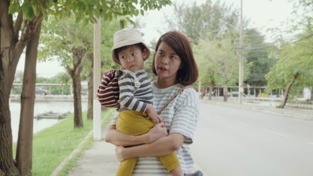 vidéos et rushes de jeune mère se promène avec son fils sur le trottoir - son