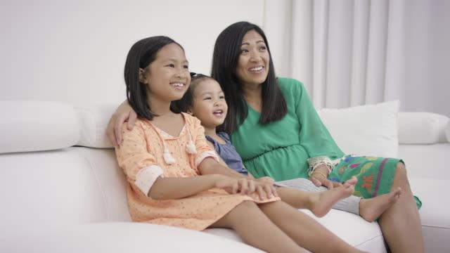 Giovane madre guardando la televisione con i bambini