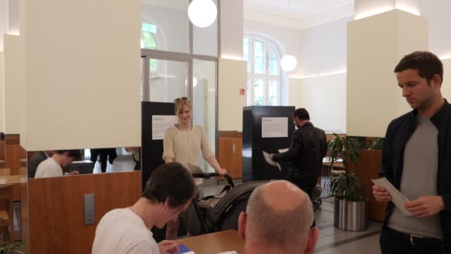 young mother with a pram presents her identity card at a polling station in european parliamentary elections on may 26, 2019 in berlin, germany.... - identity stock-videos und b-roll-filmmaterial