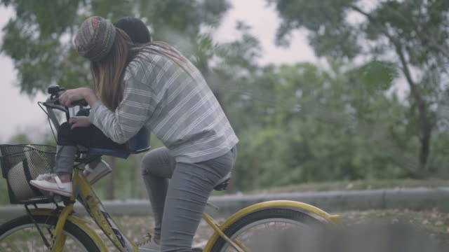 young mother with daughter cycling in the park - figlia femmina video stock e b–roll