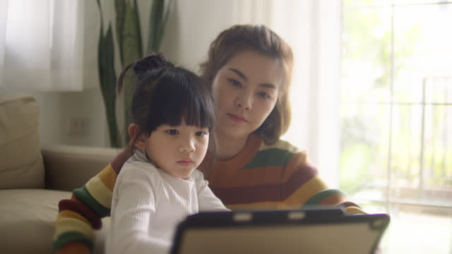 young mother with daughter doing homework on digital tablet at home. - epidemic stock videos & royalty-free footage