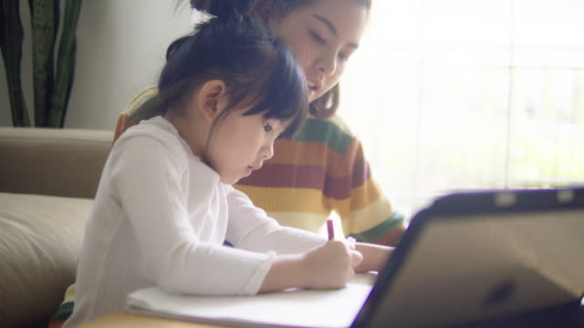 young mother with daughter doing homework on digital tablet at home. - single parent family stock videos & royalty-free footage
