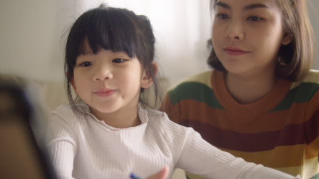 young mother with daughter doing homework on digital tablet at home. - single mother stock videos & royalty-free footage