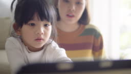Young mother with daughter doing homework on digital tablet at home.