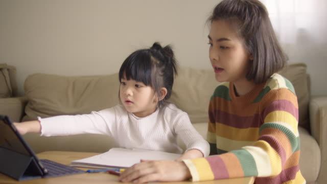 stockvideo's en b-roll-footage met jonge moeder met dochter die thuis thuis huiswerk doet op digitale tablet. - thuisonderwijs