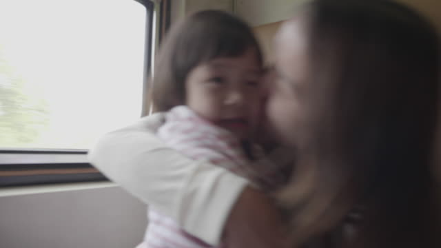 vídeos de stock e filmes b-roll de young mother with daughter traveling by the train - filha