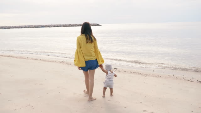 young mother with her baby (6-11months) on the beach - 6 11 months stock videos & royalty-free footage