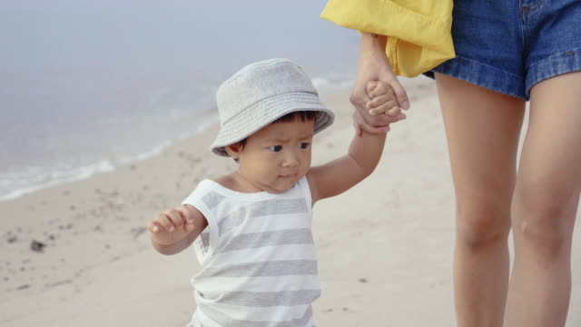 vídeos de stock e filmes b-roll de young mother with her baby (6-11months) on the beach - 6 11 meses