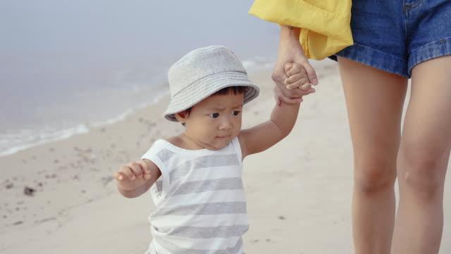 vídeos y material grabado en eventos de stock de joven madre con su bebé (6-11months) en la playa - 6 11 meses