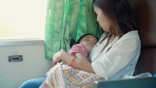 電車の中で移動中に寝て彼女の小さな娘の若い母親 - 内部点の映像素材/bロール