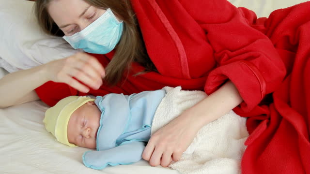 vidéos et rushes de jeune mère avec bébé nouveau-né - masque de chirurgien