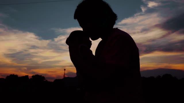 vídeos de stock, filmes e b-roll de jovem mãe com o filho, beijando o pôr do sol. - encarando