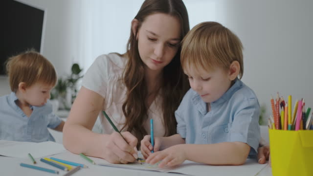A young mother with two children sitting at a white table draws colored pencils on paper helping to do homework
