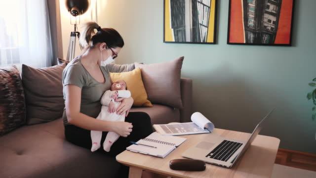 vídeos de stock, filmes e b-roll de jovem mãe com dois meses de idade bebê negociando ações de casa - variação