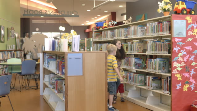 ws pan young mother with two small children enter kids section in public library filled with childrens books / rancho mirage, california, usa - 公共図書館点の映像素材/bロール