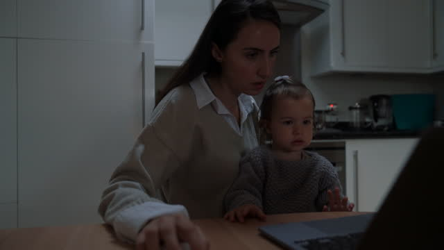 young mother working at home with her daughter - stay at home mother stock videos & royalty-free footage