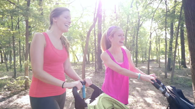 Young mothers exercising together in park, pushing toddlers in strollers