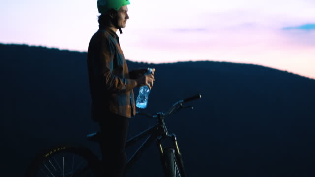 Young mountain bike cyclist drinking water at sunset.
