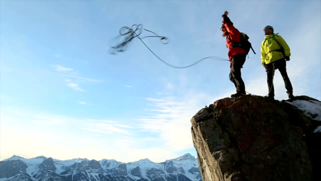 Young mountaineers throw rope off cliff face to valley below