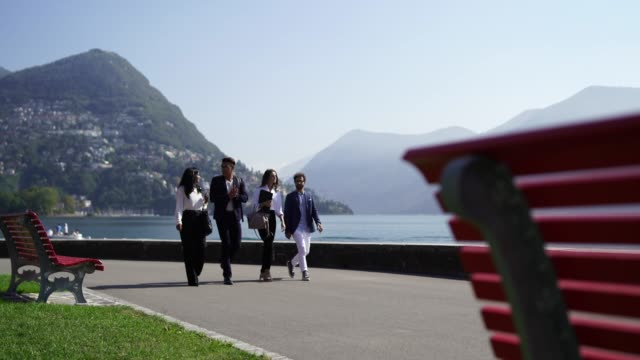 young multi ethnic business men and women walking along lake in park - ticino canton stock videos and b-roll footage
